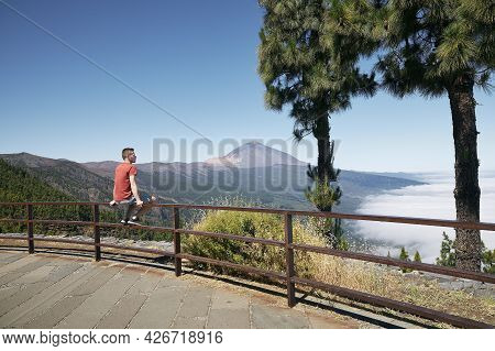 Man Sitting On Railing And Looking To Beautiful Landscape Above Clouds Against Pico De Teide. Teneri