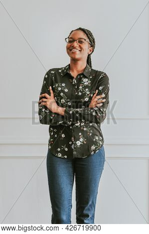 Happy empowering black woman standing by a white wall