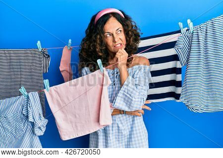 Middle age hispanic woman doing laundry at clothesline thinking concentrated about doubt with finger on chin and looking up wondering