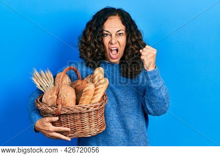 Middle age hispanic woman holding wicker basket with bread annoyed and frustrated shouting with anger, yelling crazy with anger and hand raised