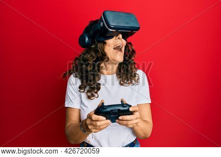 Middle age woman wearing virtual reality glasses playing 3D videogames, watching futuristic simulation, excited experience