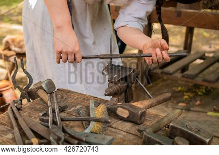 Professional Blacksmith Woman In Historical Costume Working With Metal On Anvil At Outdoor Workshop