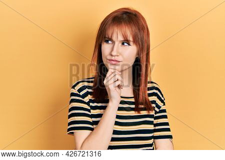 Redhead young woman wearing casual striped t shirt thinking concentrated about doubt with finger on chin and looking up wondering