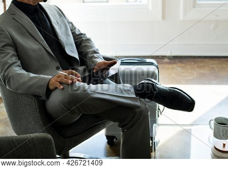 Businessman using a stylus with his digital tablet in an airport lounge