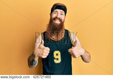 Redhead man with long beard wearing basketball uniform success sign doing positive gesture with hand, thumbs up smiling and happy. cheerful expression and winner gesture.