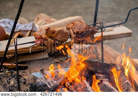 Process Of Cooking Large Meat Peaces On Spit Over Open Fire At Historical Festival - Close Up View.