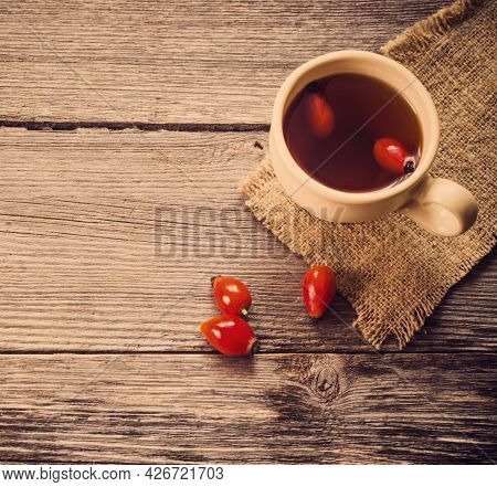 Cup Of Tea With Hip Roses, On Wooden Table