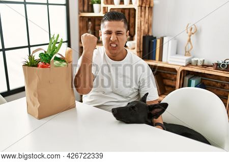 Young hispanic man sitting with paper bag with groceries annoyed and frustrated shouting with anger, yelling crazy with anger and hand raised