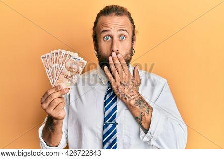 Handsome business man with beard and long hair holding 50 turkish lira banknotes covering mouth with hand, shocked and afraid for mistake. surprised expression