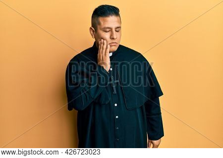 Young latin priest man standing over yellow background touching mouth with hand with painful expression because of toothache or dental illness on teeth. dentist