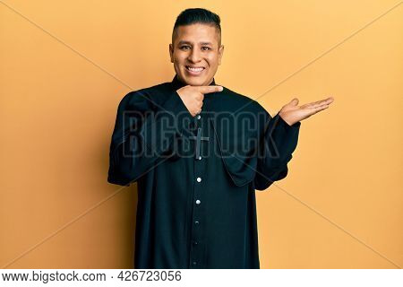 Young latin priest man standing over yellow background amazed and smiling to the camera while presenting with hand and pointing with finger.