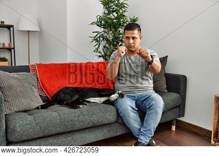 Young latin man and dog sitting on the sofa at home punching fist to fight, aggressive and angry attack, threat and violence