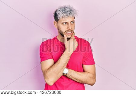 Young hispanic man with modern dyed hair wearing casual pink t shirt thinking worried about a question, concerned and nervous with hand on chin