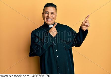 Young latin priest man standing over yellow background smiling and looking at the camera pointing with two hands and fingers to the side.