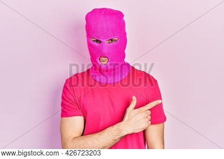Young hispanic man with modern dyed hair wearing pink balaclava mask face smiling cheerful pointing with hand and finger up to the side