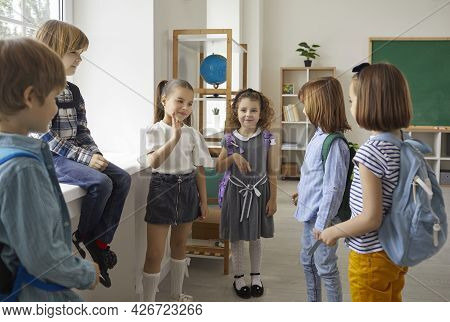 Elementary Schoolchildren Group Talking During Break Standing In Classroom