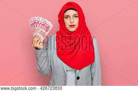 Beautiful hispanic woman wearing islamic hijab holding chinese yuan banknotes thinking attitude and sober expression looking self confident