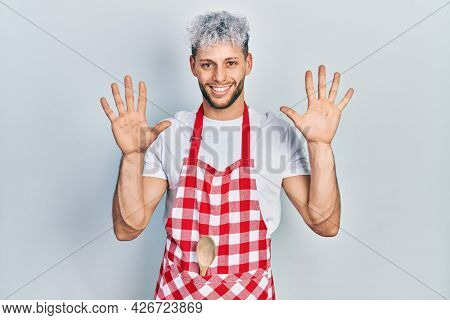 Young hispanic man with modern dyed hair wearing apron showing and pointing up with fingers number ten while smiling confident and happy.