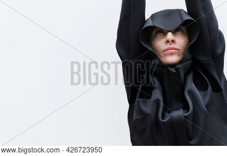 Woman in a cool black hoodie put her hands up in the air