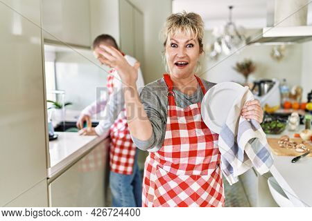 Middle age caucasian couple wearing apron washing dishes at home celebrating victory with happy smile and winner expression with raised hands