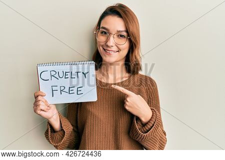 Young caucasian woman holding cruelty free message paper smiling happy pointing with hand and finger