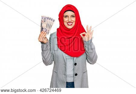 Beautiful hispanic woman wearing islamic hijab holding japanese yen banknotes doing ok sign with fingers, smiling friendly gesturing excellent symbol