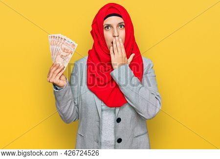 Beautiful hispanic woman wearing islamic hijab holding turkish lira banknotes covering mouth with hand, shocked and afraid for mistake. surprised expression