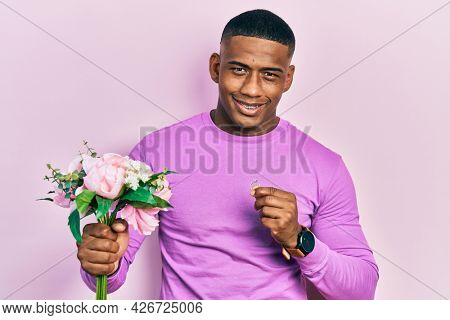 Young black man holding bouquet of flowers and wedding ring smiling and laughing hard out loud because funny crazy joke.