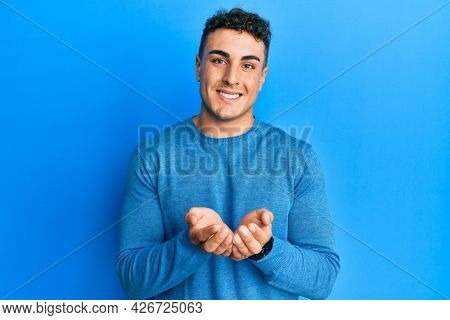 Hispanic young man wearing casual winter sweater smiling with hands palms together receiving or giving gesture. hold and protection