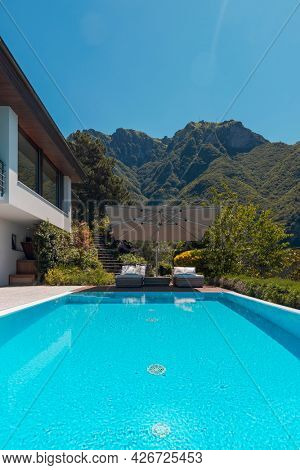 Modern two-story house with large pool overlooking the mountains. Two sunbeds and a large open umbrella to enjoy vacation. Nobody inside