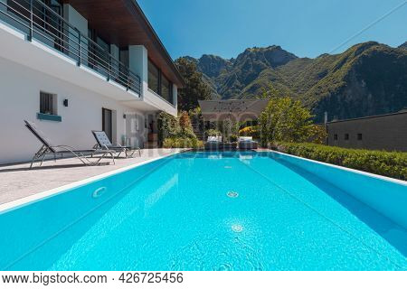 Modern two-story house with large pool overlooking the mountains. Two chaise lounges to enjoy the sun, two sunbeds and a large open umbrella to enjoy vacation. Nobody inside
