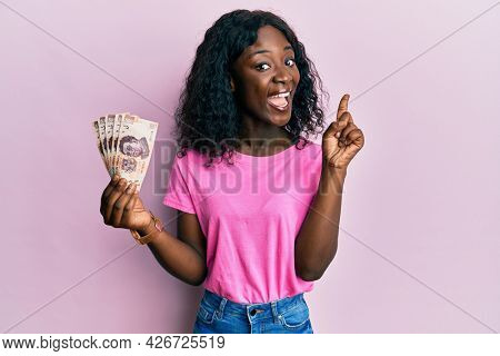 Beautiful african young woman holding 500 mexican pesos banknotes smiling with an idea or question pointing finger with happy face, number one