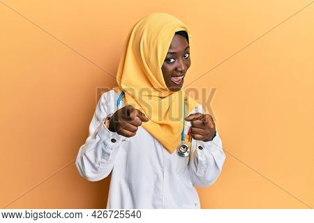 Beautiful african young woman wearing doctor uniform and hijab pointing fingers to camera with happy and funny face. good energy and vibes.
