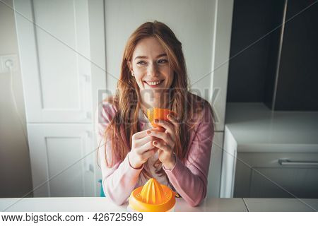 Ginger Woman With Freckles Is Smiling While Holding A Sliced Orange While Squeezing Fruit Juice