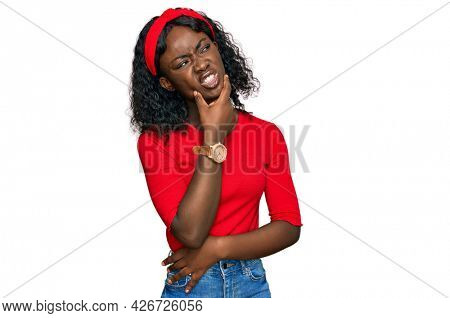 Beautiful african young woman wearing casual clothes thinking worried about a question, concerned and nervous with hand on chin