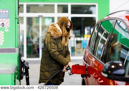 Woman Wear Medical Mask At Self-service Gas Station, Hold Fuel Nozzle, Refuel The Car With Petrol Du