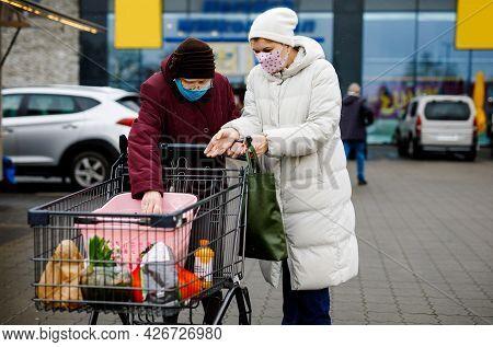 Senior Woman And Social Worker With Medical Mask Due Pandemic Coronavirus Disease. Daughter Or Grand