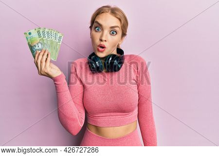 Beautiful blonde caucasian woman wearing gym clothes holding chilean pesos scared and amazed with open mouth for surprise, disbelief face