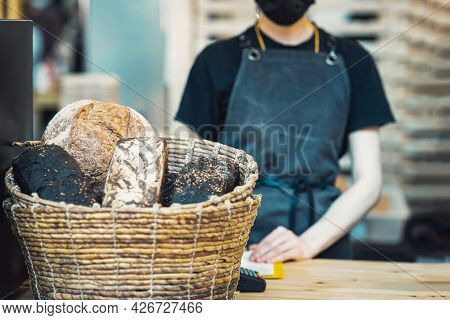 Wicker Basket With Different Types Of Bread Close-up On A Blurred Background Girl Seller. Sale Of Fl