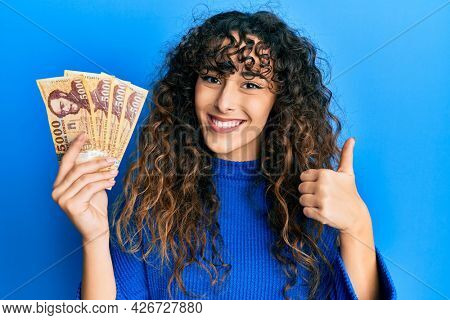 Young hispanic girl holding 5000 hungarian forint banknotes smiling happy and positive, thumb up doing excellent and approval sign