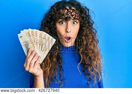 Young hispanic girl holding 100 danish krone banknotes scared and amazed with open mouth for surprise, disbelief face