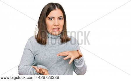 Young beautiful woman wearing casual turtleneck sweater disgusted expression, displeased and fearful doing disgust face because aversion reaction.