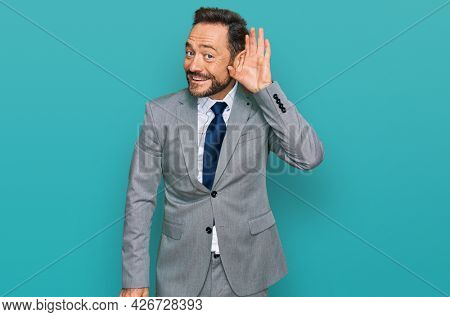 Middle age man wearing business clothes smiling with hand over ear listening an hearing to rumor or gossip. deafness concept.