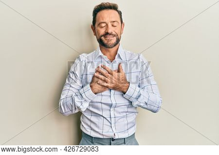 Middle age man wearing business clothes smiling with hands on chest with closed eyes and grateful gesture on face. health concept.