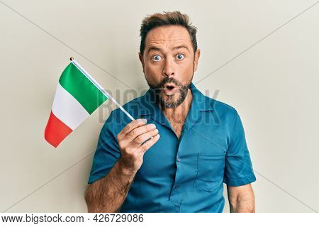 Middle age man holding italy flag scared and amazed with open mouth for surprise, disbelief face