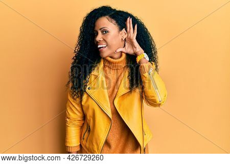 Middle age african american woman wearing wool winter sweater and leather jacket smiling with hand over ear listening an hearing to rumor or gossip. deafness concept.