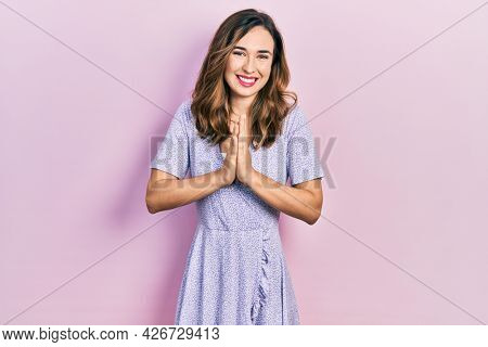 Young hispanic girl wearing casual clothes praying with hands together asking for forgiveness smiling confident.