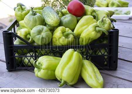 Vegetables In A Black Box Close-up. Fresh Peppers, Cucumbers And Tomatoes In A Box On A Wooden Backg