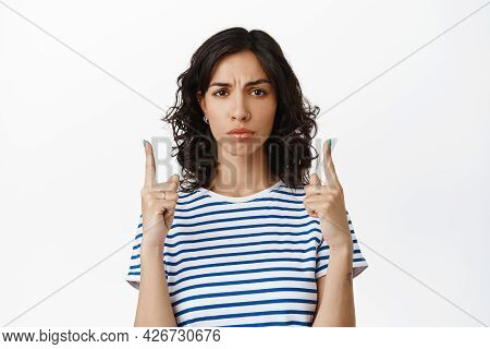 Concerned Brunette Girl Frowning, Pointing Fingers Up And Look Upset, Disappointed With Bad Advertis