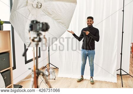 Young hispanic man with beard posing as model at photography studio amazed and smiling to the camera while presenting with hand and pointing with finger.